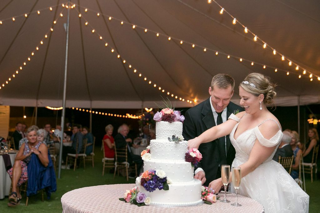 Bride and Groom celebrating their wedding by cutting a multilayered Wedding Cake under a canopy and lighting decorations
