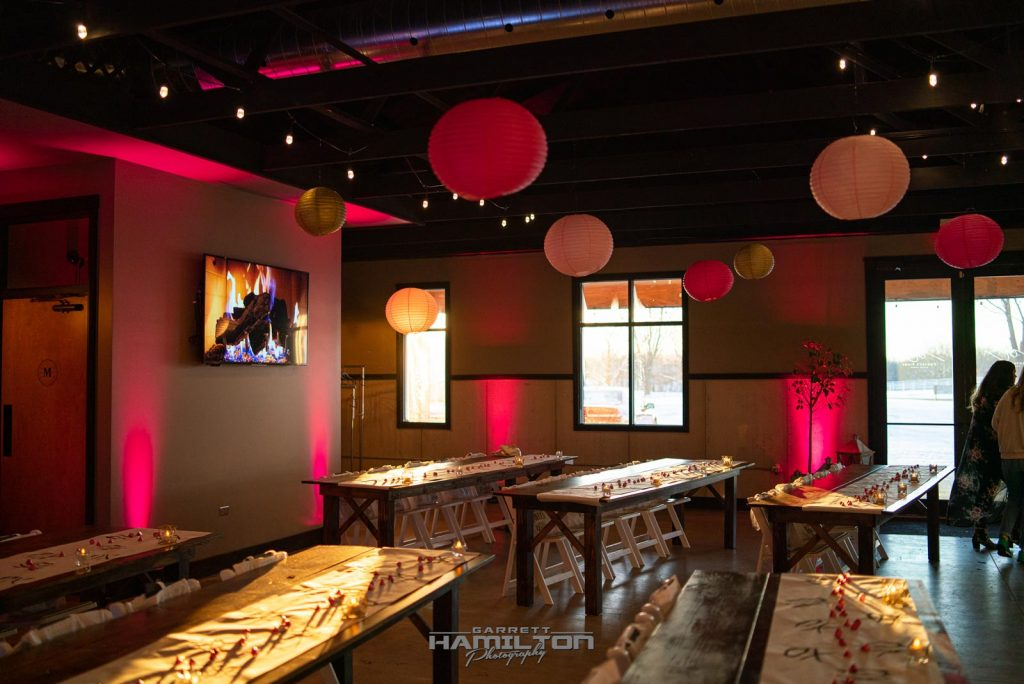 Event Decorations with a pink lighting theme, pink overhead lamps and long tables lined up with chairs